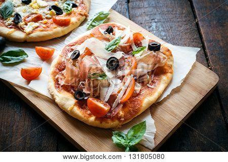Served prosciutto mini pizza on rustic background