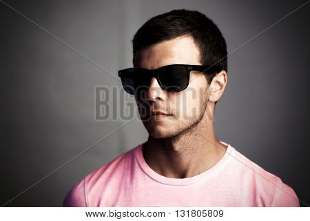 Dark portrait of a young man in sunglasses, social isolation and anonymity concept.