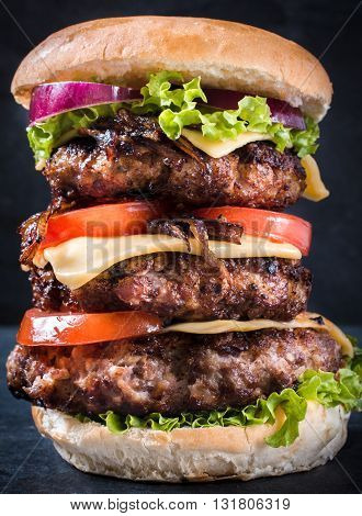 Photos of triple cheesburger on rustic background