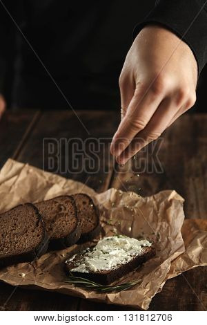 Hand pours some herb spicies on sandwich with rustic bread and soft goat cheese with herbs near slices of homemade luxury rye bread with figs and rosemary spice on craft paper on wooden table