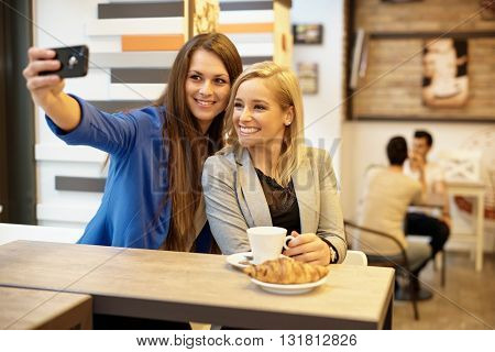 Happy attractive girls making self portrait by mobilephone in cafeteria.