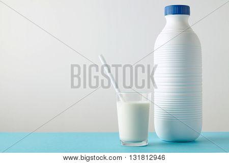Transparent Glass With Fresh Organic Milk And White Drinking Straw Inside Near Blank Riffled Plastic