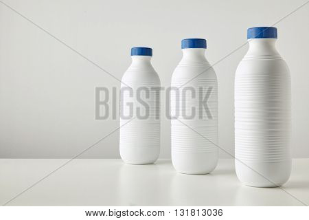 Three Blank White Plastic Riffled Bottles With Blue Caps In Row Isolated On Table Space For Your Tex