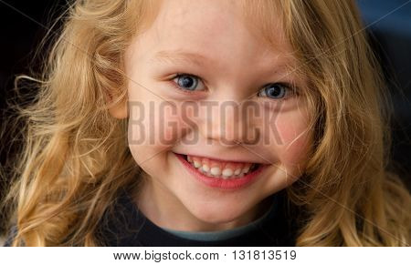 close up of a 4 year old child with blonde hair and blue eyes happily smiling up at the camera