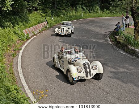 PASSO DELLA FUTA (FI) ITALY - MAY 21: driver and co-driver on a classic German car BMW 328 (1938) travel in Tuscany during the classic car race Mille Miglia on May 21, 2016 in Passo della Futa (FI) Italy