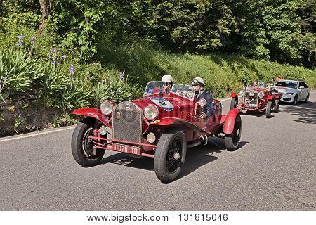 PASSO DELLA FUTA (FI) ITALY - MAY 21: driver and co-driver on an old Italian car Lancia Lambda tipo 221 Spider Casaro (1928) travel in Tuscany during the historic race Mille Miglia on May 21, 2016 in Passo della Futa (FI) Italy