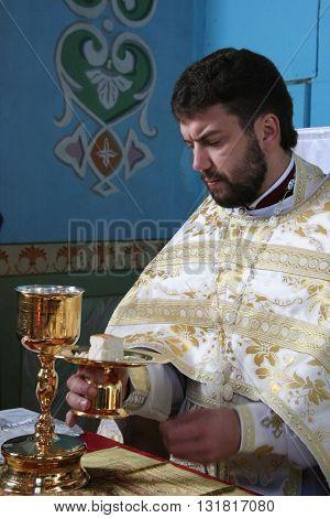 LUTSK UKRAINE - JANUARY 08 - Priest consecrates bread during orthodox liturgy ceremony in Lutsk on January 08 2009.