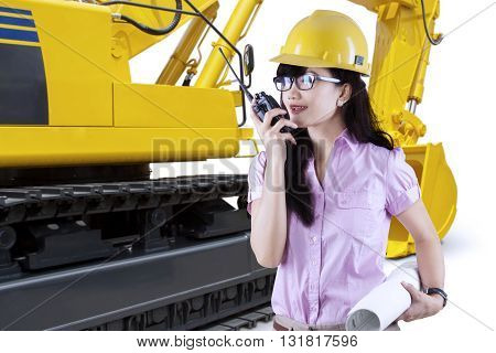 Portrait of a female developer talking on the walkie talkie with an excavator background isolated on white background