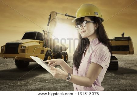 Young forewoman working in the mining site while wearing helmet and using digital tablet with excavator on the background
