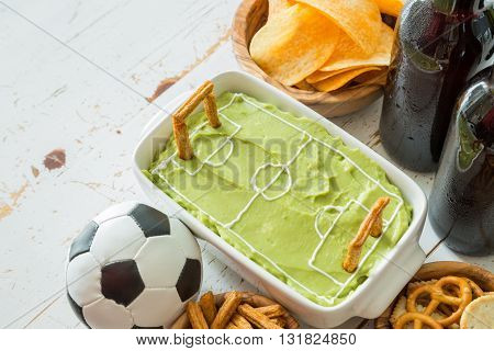 Selection of party food for watching football championship, soccer field dip