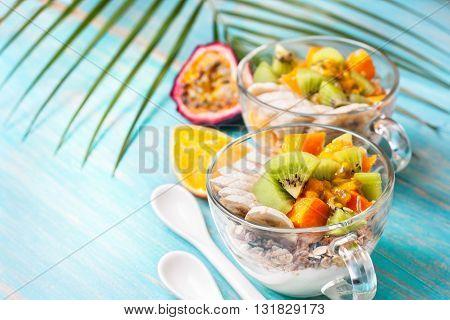 Dietary breakfast. Muesli yoghurt tropical fruits: mango kiwi pineapple passion fruit in cup on a blue background