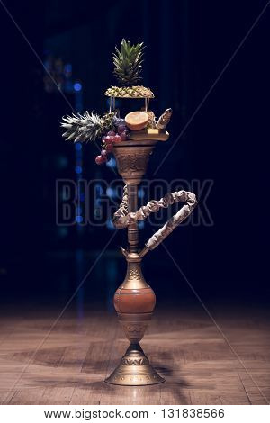 Exotic hookah. Different hookah over the bright backgrounds with smoke. Hookah with fruit flavour on wooden table in vintage style