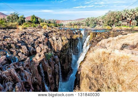 View of Epupa falls on the border of Namibia and Angola. The falls are created by the Kunene River in the Kaokoland area. Is 0.5 km wide and drops in a series of waterfalls spread over 1.5 km.