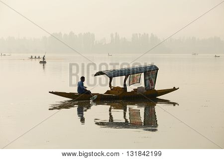 SRINAGAR INDIA - JULY 07 2015 : Lifestyle in Dal lake local people use 'Shikara' a small boat for transportation in the lake of Srinagar Jammu and Kashmir state India
