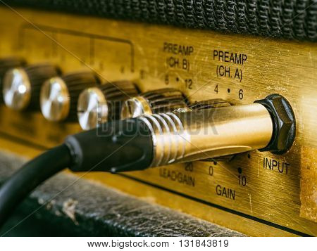 Macro photo of a vintage electric guitar amplifier showing the knobs and input plug. Selective focus on the word input.