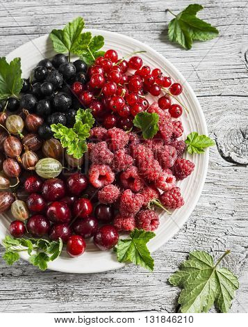 Assortment of berries - raspberries gooseberries red currants cherries black currants on a white plate on a light rustic wooden background. Healthy food delicious summer dessert