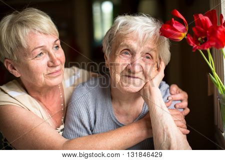 Portrait of an elderly woman of eighty years with her daughter.