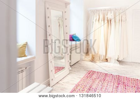 Collection of wedding dresses and big mirror in showroom