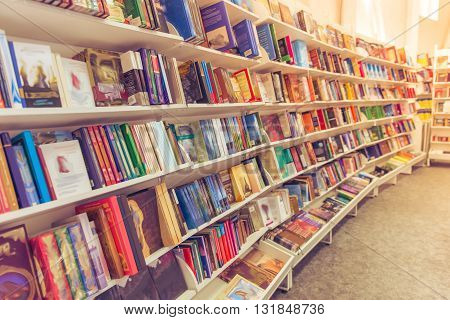Rows of different colorful book lying on the shelves in the modern urban bookshop