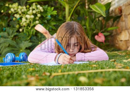Blond kid girl homework lying on grass turf writting notebook