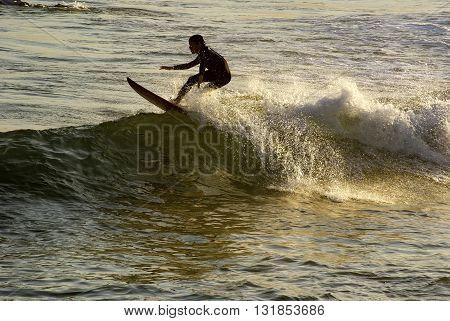 Boy surfing at Arpoador beach in Ipanema