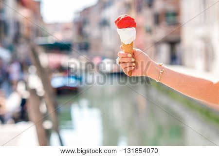 Holding traditional italian ice cream called Gelato in the waffle cone on Venice canal background in Italy.