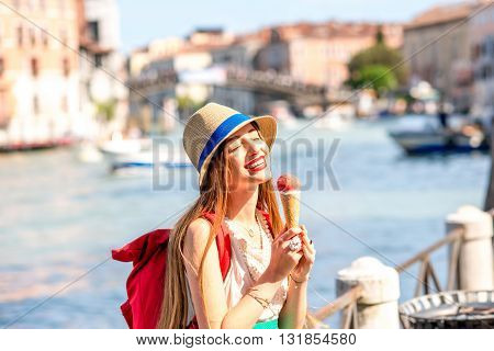 Young female traveler eating traditional italian ice cream called Gelato in the waffle cone in Venice.