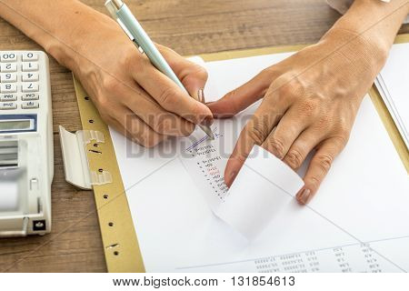 Low angle view of female accountant summing up the numbers writing on a printout receipt while making financial report.