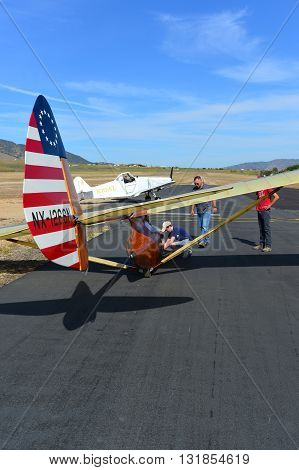TEHACHAPI, CA - MAY 28, 2016: A tow plane taxis into position and hooks up to a Bowlus BA-100 Baby Albatross glider during the Western Vintage/Classic Regatta at Mountain Valley Airport.