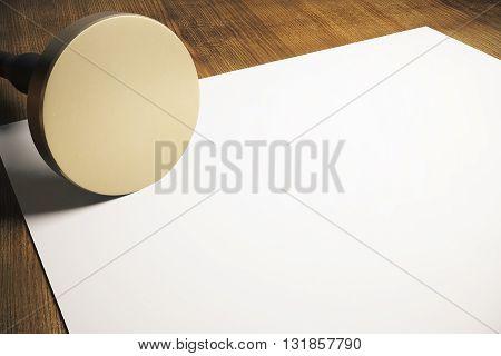 Golden round stamper and blank paper sheet on wooden background. Mock up 3D Rendering