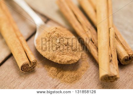 Ground cinammon on a silver spoon with cinammon sticks on a wooden background