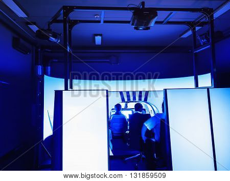 Room with an installed flight simulator for small private airplanes blue colored. General view of the cabin.