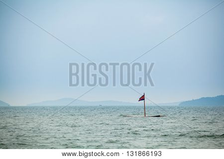 Summer seascape with cambodian flag on tropical beach in Sihanoukville in Cambodia. Landscape of south east Asia.