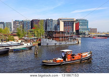 AMSTERDAM, NETHERLANDS - MAY 6, 2016: Beautiful harbor cityview with boats and modern buildings in Amsterdam Netherlands.