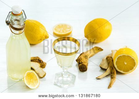 Home ginger tincture in a glass and fresh lemons on the white wooden background in rustic style, selective focus