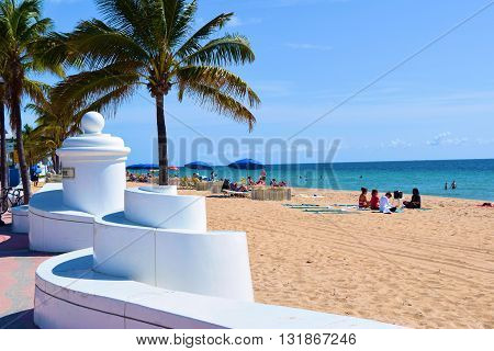 May 20, 2016 in Ft Lauderdale, FL:  White wall next to the sandy Ft Lauderdale Beach where tourists and locals enjoy sunbathing and relaxing on the sand and lounge chairs surrounded by Palm Trees and the Atlantic Ocean taken in Ft Lauderdale, FL