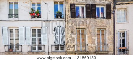 Facades of old buildings with windows shutters and a small balcony in a provincial European town