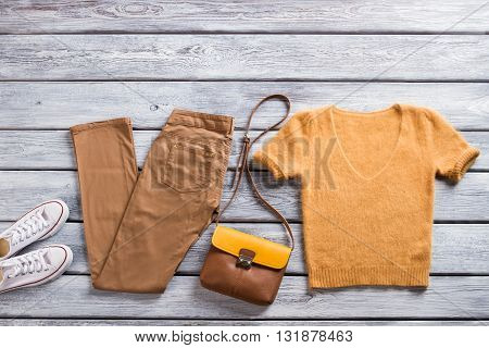 Brown pants and t-shirt. White shoes and bicolor bag. Woolen top with v-neck. Clothing items for stylish women.