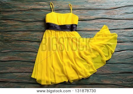 Casual yellow dress with straps. Black insert on yellow garment. Dress lying on green table. Light fabric and simple design.