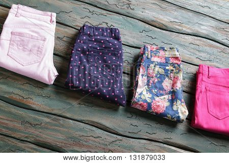 Blue floral pattern trousers. Light pink folded pants. Imported clothing of high quality. Lady's fashionable trousers for spring.