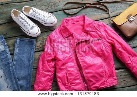 Pink jacket and white shoes. Jeans and brown bicolor bag. Girl's new outerwear on shelf. Stylish jacket from brand store.