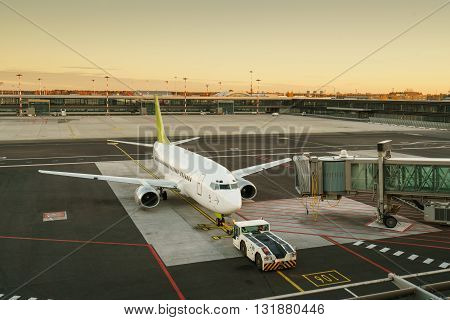 Airplane at the terminal gate ready for takeoff - Modern international airport during sunrise - Concept of emotional travel around the world
