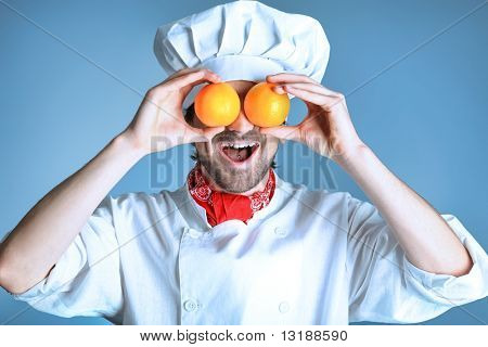 Portrait of a man cook holding oranges. Shot in a studio over grey background.