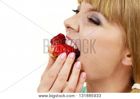 Woman holds cake cupcake in hand taking a huge bite out of dessert eating unhealthy junk food. Sweetness indulging and fattening concept