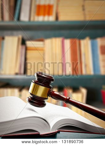 Judge gavel and book on table on book shelves background