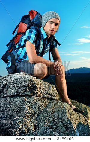 Young man tourist is sitting at the top of a mountain with a feeling of freedom.