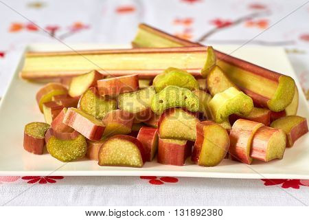 freshly cut pieces of rhubarb on an white plate
