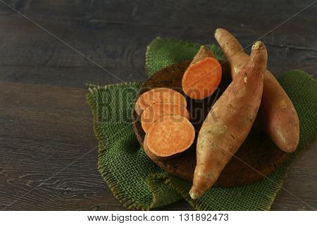 Raw sweet potatoes, yams, on wooden background
