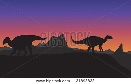 Silhouette of Iguanodon in hills at the afternoon