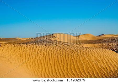 Tunisian desert landscape with blue sky. Dunes background